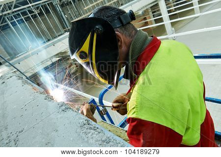 welder working with electrode at arc welding in construction site