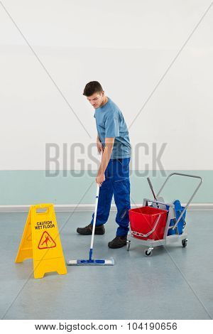 Male Worker With Cleaning Equipments Mopping Floor