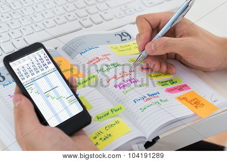 Person Hands With Mobile Phone And Diary