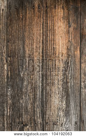 Section of an old door with wooden planks with rusty nails