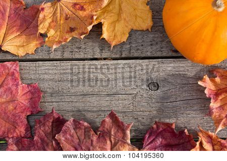 Autumn Colorful Leaves And Pumpkin On Wooden Table