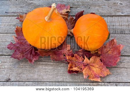 Pumpkins With Autumn Colorful Leaves On Wooden Table
