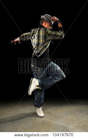 African American hop hop dancer performing over dark background