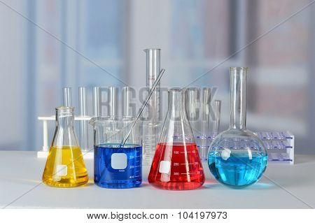 Laboratory table with glassware with liquids of different colors