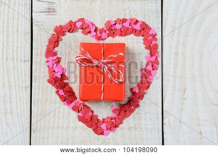 Tiny paper hearts scattered in the shape of a Heart with a red gift in the middle. Valentines Day Concept.
