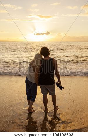 Honeymoon Couple in love watching a sunset at the beach together