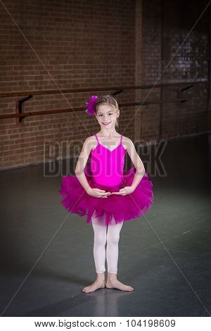 Beautiful little dancer portrait at a dance studio. Vertical photo in a traditional dance studio. Lots of copy space above