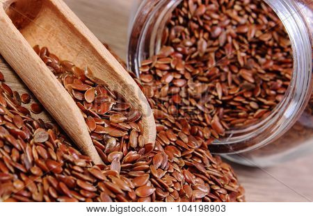 Linseed Spilling Out Of Jar On Wooden Background