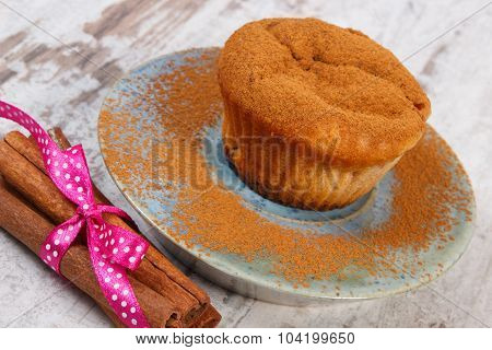 Muffins With Powdery Cinnamon, Cinnamon Sticks On Wooden Background, Delicious Dessert