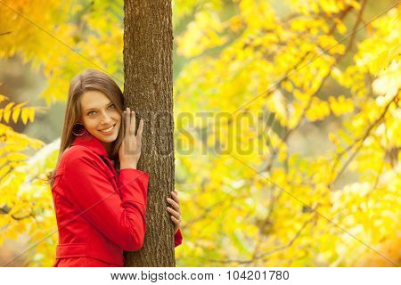 Young woman with red coat in autumn forest