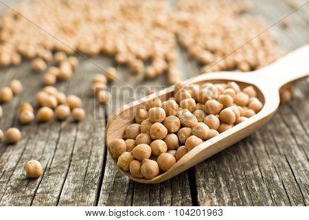 uncooked chickpeas in wooden scoop