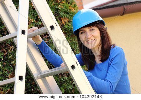 Smiling Woman In Blue Helmet Climbing On Aluminum Ladder