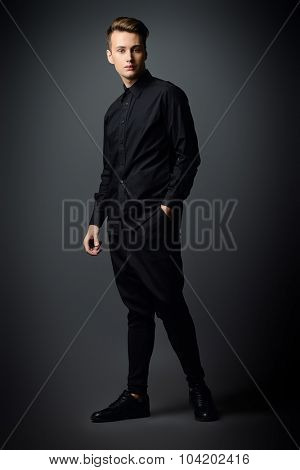 Full length portrait of a handsome male model in black clothes posing at studio. Men's beauty, fashion.