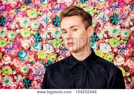 Beautiful young man over floral background. Men's beauty, fashion.