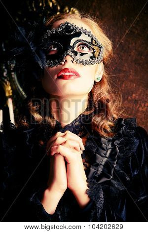 Close-up portrait of a beautiful praying lady in black mask and black medieval dress. Vampire. Halloween concept. Vintage style.