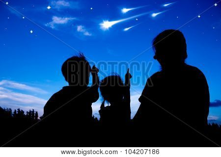 Silhouette Of Happy Family Sitting And Looking Sky At Comets.