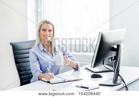Young, attractive and confident business woman working in office