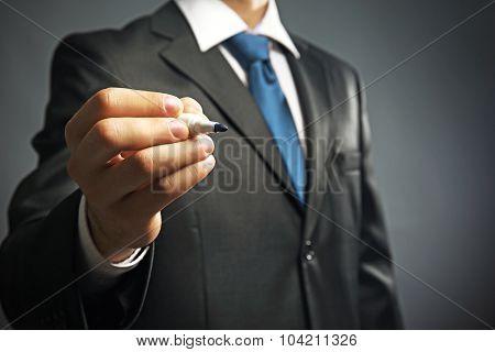 Businessman holding marker on gray background