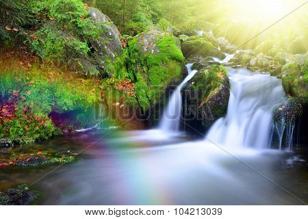 Waterfall on a mountain creek with rainbow.
