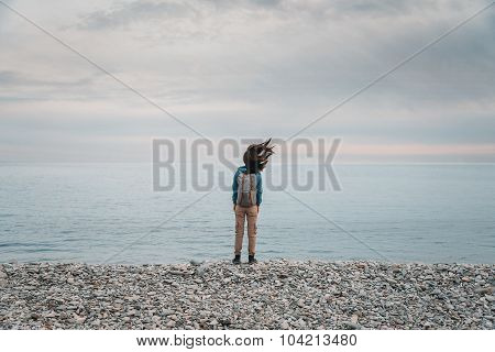 Traveler Woman Standing On Coast In Windy Weather