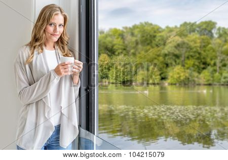 Woman having a coffee, looking through the window to a lake landscape