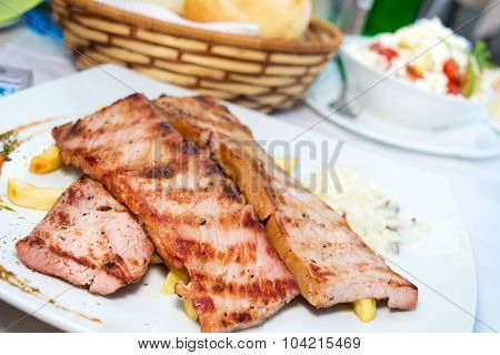 Grilled smoked steak served with french fries in a restaurant