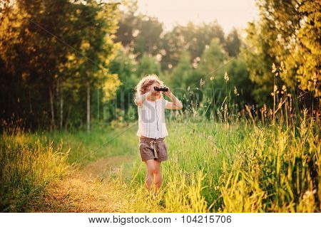 child girl watching birds with binocular on the walk in summer sunny forest