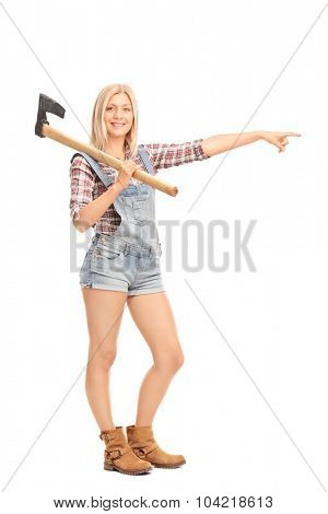 Full length portrait of a young woman in overalls holding an axe and pointing to the right with her hand isolated on white background