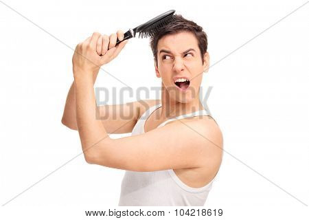 Studio shot of an angry young man with a hairbrush stuck in his hair isolated on white background