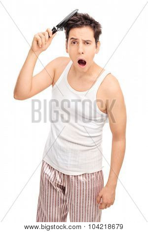 Sleepy guy combing his hair with a hairbrush and yawning while looking at the camera isolated on white background