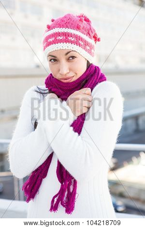 Smiling woman wearing a scarf and hat outside