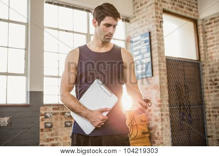 Instructor holding clipboard and stopwatch at the gym