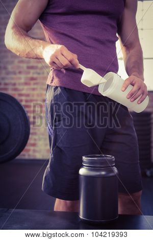 Midsection of man putting supplement into bottle at the gym