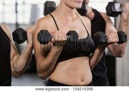 Midsection of people lifting dumbbell at the gym