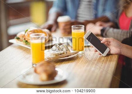 Cropped image of woman using phone while having breakfast with colleagues in office