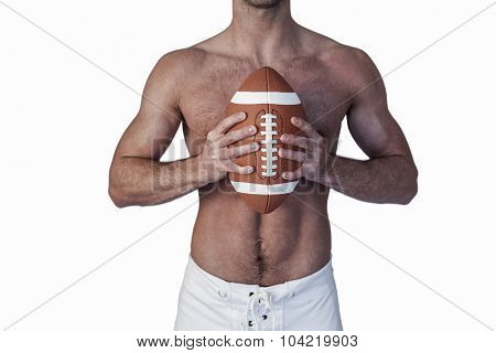 Midsection of shirtless rugby player holding ball over white background