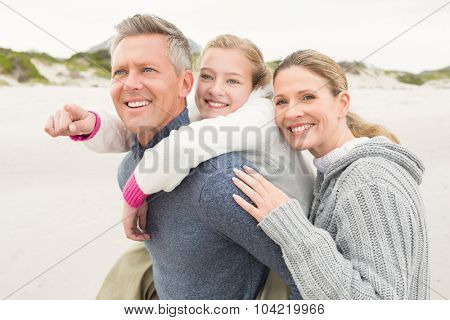 Father carrying his daughter with mother beside them
