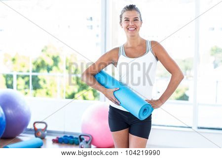 Portrait of woman holding yoga mat with hand on hip in fitness studio