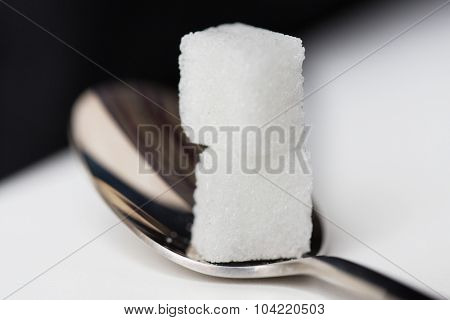 food, junk-food, diabetes and unhealthy eating concept - close up of white sugar cubes on teaspoon