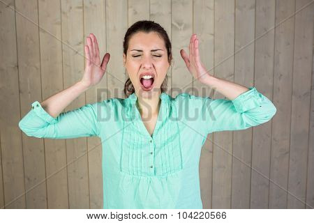 Screaming woman gesturing with eyes closed while standing by wall at home