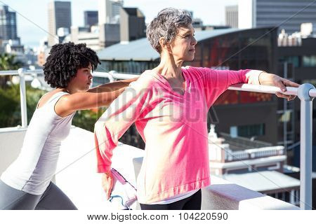 Mature woman stretching with female friend by railing against buildings