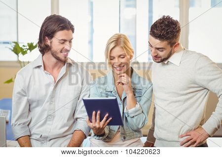Smiling businesswoman holding laptop standing with male colleagues in creative office