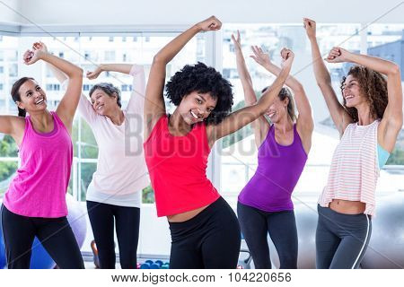 Happy women exercising with arms raised in fitness studio