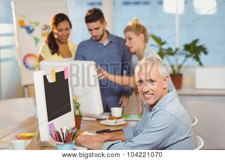 Portrait of confident businessman using on computer with colleagues working in background in creative office