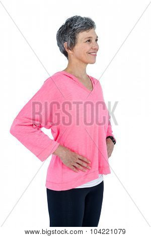 Happy mature woman with hand on hip standing against white background