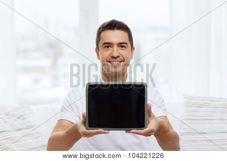 technology, people and lifestyle, distance learning concept - happy man showing tablet pc computer black blank screen at home