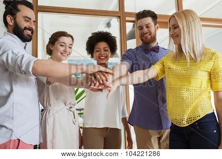business, startup, gesture, people and teamwork concept - happy creative team with hands on top of each other in office
