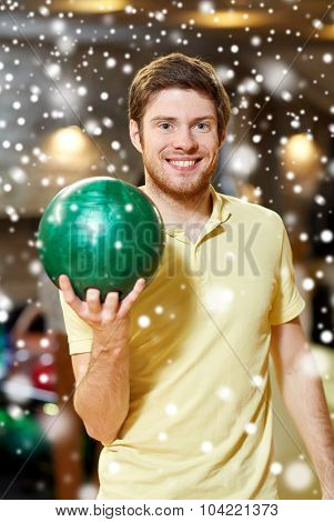 people, leisure, sport and entertainment concept - happy young man holding ball in bowling club at winter season