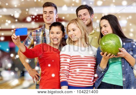 people, leisure, sport, friendship and entertainment concept - happy friends taking selfie with smartphone in bowling club at winter season
