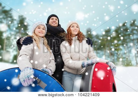 winter, leisure, sport, friendship and people concept - group of smiling friends with snow tubes outdoors